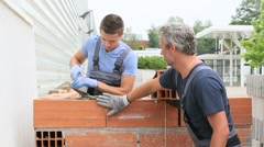 Mason with trainee in construction, building wall - stock footage
