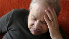 Sad old woman sitting pensive on the sofa Stock Footage
