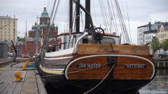 Wooden sailing vessel in  Helsinki Marina with orthodox cathedral Stock Footage