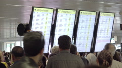 People waiting at the airport in front of the time tables Stock Footage