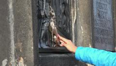 People touching the statue of Saint John of Nepomuk in Prague Stock Footage