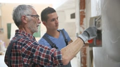 Young apprentice with professional plasterer - stock footage