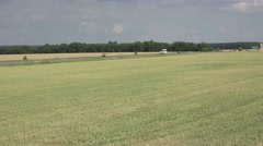 Road through farm field of wheat. Traffic Car. Central Europe Stock Footage