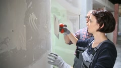 Young woman apprentice with professional plasterer - stock footage