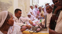 A doctor conducts a medical examination of older women outdoors in central India Stock Footage