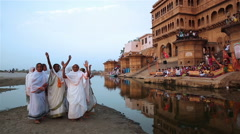 Stock Video Footage of Indian women dancing and praise Krishna on the banks of river near old temple.