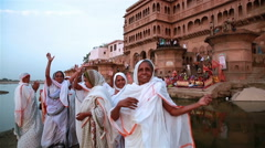 Indian women dancing and praise Krishna on the banks of river near old temple. - stock footage