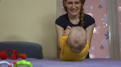 Tender woman with cute baby make sit-up exercises on sofa. 4K Stock Footage