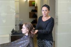 Hairstylist Woman Fixing Hair of a Female Customer - stock photo