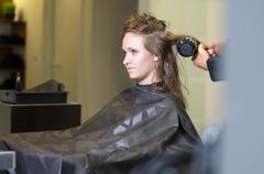Teen Girl In Salon Drying her Hair with Blow Dryer - stock photo