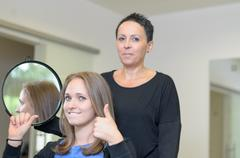 Pretty smiling 20s woman at hairdressers - stock photo