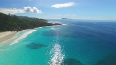 Aerial view blue and turqoise ocean with tropical island Stock Footage
