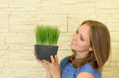 Happy Woman Holding a Small Green Plant Stock Photos
