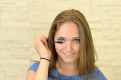 Pretty young woman applying eyeliner - stock photo