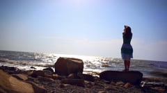 Young woman  is standing at seascape background on stone and rises her hands Stock Footage