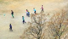 Boys play football on the dirt field Stock Footage