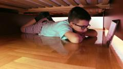 Stock Video Footage of Boy lying under the bed and watching cartoons - slider shoot