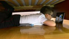 Boy lying under the bed and watching cartoons - slider shoot Stock Footage