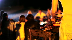 Young people make a barbecue on the beach at night - stock footage