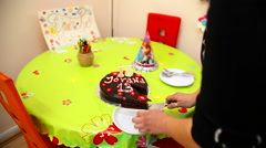 Mother cuts birthday chocolate cake for daughter Stock Footage
