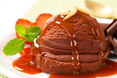 Scoop of chocolate ice cream with caramel syrup - stock photo