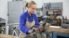 Young woman apprentice in ironworks - stock footage