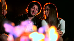 Young man and woman sitting by the fire at night and talking Stock Footage