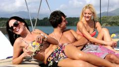 Men and women lying on the deck of a yacht and enjoy on the sun - stock footage