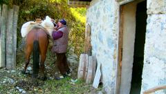 Man puts a sack with milled flour on the horseback Stock Footage