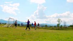 Men play football on the village playground Stock Footage