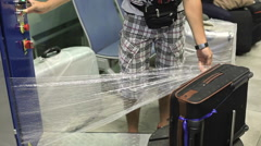 Man wrapped bag with a protective nylon at the airport RG Stock Footage