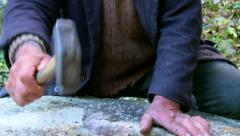 Old miller sharpening a stone mill with a hammer - stock footage