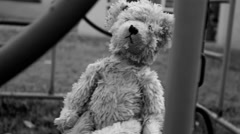 Creepy teddy bear on a swing Stock Footage