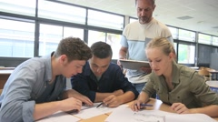 Teacher with group of students working on digital tablet Stock Footage