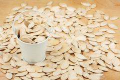 White bucket with pumpkin seeds  on the wooden floor - stock photo