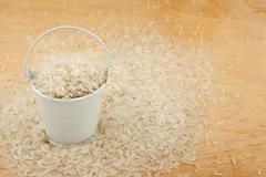 White bucket of rice on the wooden floor - stock photo
