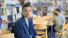 Student boy sitting on table in library room - stock footage