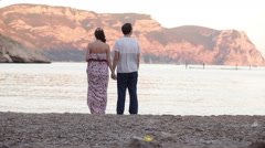 Couple, a man and woman holding hands while standing on the beach lookin Stock Footage