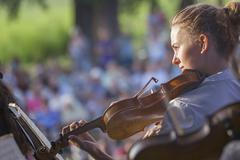 Stock Photo of Young woman playing the violin at outdoors