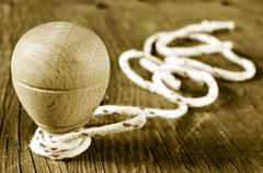 Wooden spinning top with a string coiled in its axis, in sepia toning Stock Photos