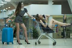 Young women with shopping trolley and bag Stock Photos