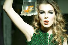 Tempting girl with goldfish - stock photo