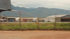 Pan Shot of US C-130 with Mountains in Background Stock Footage