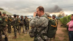 US and Columbian Paratroopers Don Parachutes and Walk to Waiting Aircraft - stock footage
