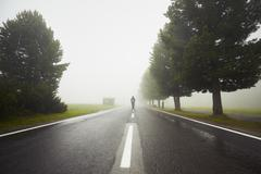 Lonely man is walking in mysterious fog - stock photo