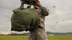 US Paratrooper Dons Pack and Helmet after Jumping Stock Footage