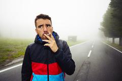 Young man is smoking on the road in mysterious fog Stock Photos