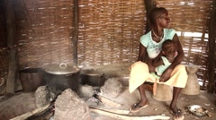 African young mother cooking and breast feeding child Guinea Bisseau Stock Footage