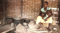 African young mother watching food cooking and breast feeding child Stock Footage