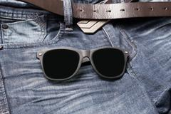 sunglasses on jean pants - stock photo